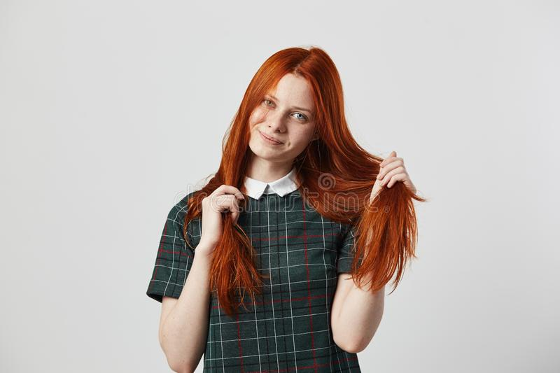 Rymmer den långhåriga flickan för den härliga rödhåriga mannen i en grön rutig klänning hennes hand på hennes hår på den vita bak arkivbilder