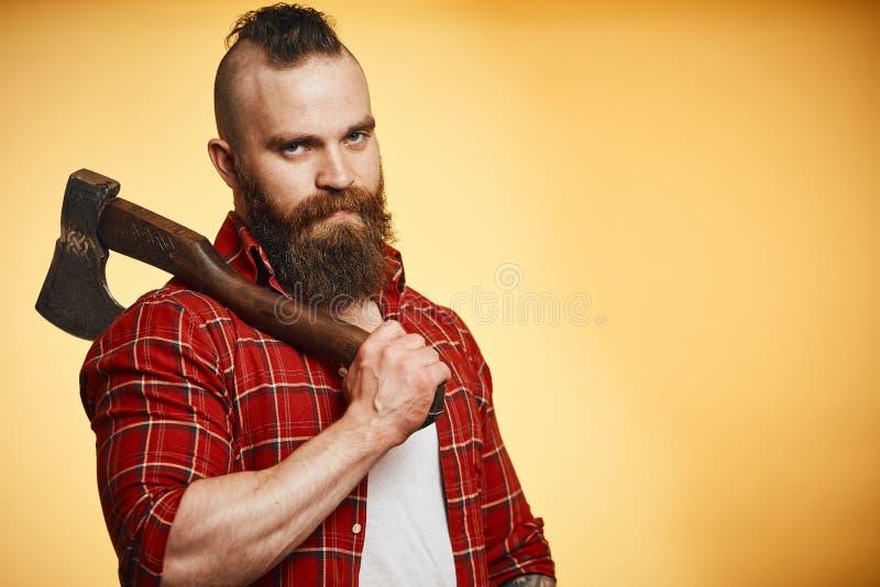 Rymmer den skäggiga mannen för Mohawk yxan på hans skuldra på gul bakgrund arkivfoto