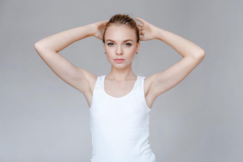 Rymmer den unga kvinnan för skönhetmodeståenden med klar hud händer bak huvudet royaltyfri foto