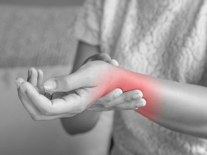 Rymmer sammanträde för den unga kvinnan för closeupen på soffan hennes handledhandskada arkivfoton
