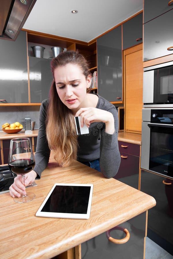 Rynka pannan den härliga unga kvinnan som tänker om hennes e-shopping på hennes minnestavla royaltyfria foton