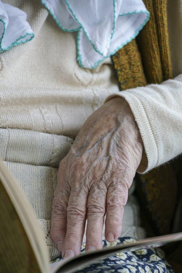 Rynkig hand av en señorkvinna som trycker på en bok, medan läsa arkivbild