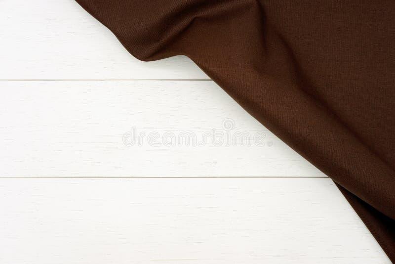 Rynkigt mörkt brunt tyg på lantlig vit träplankabakgrund royaltyfri fotografi