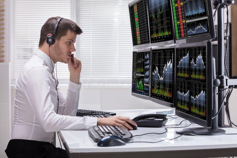 Rynku Papierów Wartościowych makler Analizuje wykresy Na ekranach komputerowych zdjęcie stock
