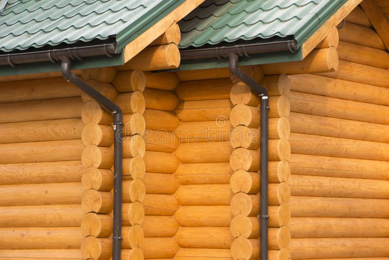 Rynna na drewnianym domu z dachem zielony bitumiczny dekarstwo zdjęcia stock