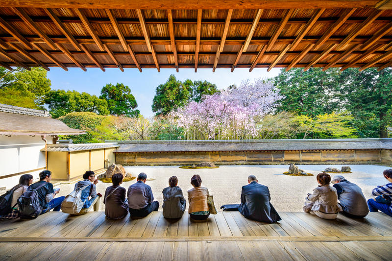 Ryoanji Temple. KYOTO, JAPAN - APRIL 9, 2014: Tourists sit and observe the spring cherry trees of Ryoan-ji Temple. The garden is considered one of the finest royalty free stock image