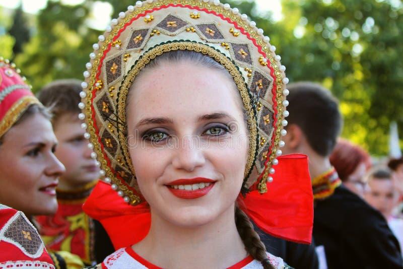 Rysk dansare i traditionell dräkt på den internationella folklorefestivalen för barn och guld- fisk för ungdom royaltyfri bild