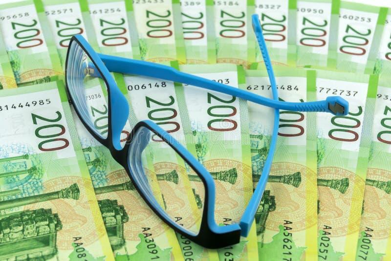Rysk kassa Många räkningar är 200 rubel på tabellen Blåa exponeringsglas är på sedlarna royaltyfri fotografi