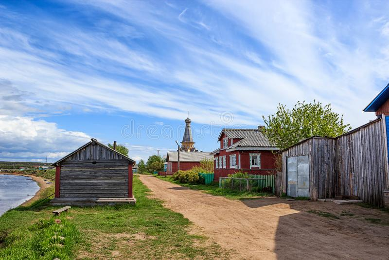 Rysk nordlig by Trähus-, kyrka-, grusväg- och flodsikt arkivbild