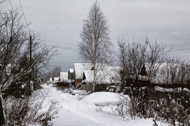 Rysk by och trähus i det i en vinter arkivfoton