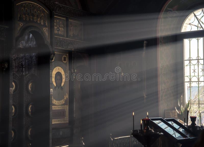 Rysk ortodoxkyrka Sun&en x27; s-strålar från fönstret exponerar symbolen av Jesus Christ på iconostasisen royaltyfri fotografi