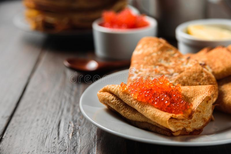 Rysk pannkakablini med den röda kaviaren royaltyfria foton