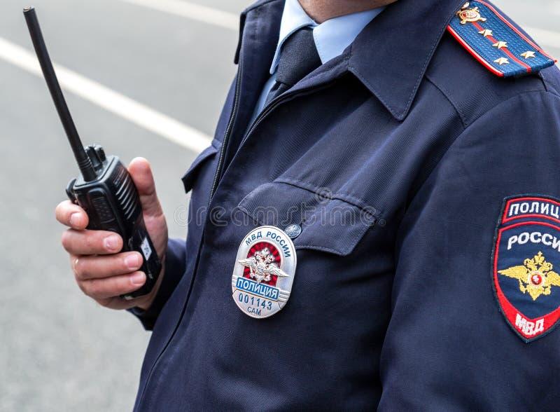 Rysk polis i likformig med emblemet och sparren arkivfoton