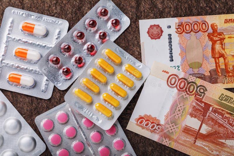 Ryska pengar och olika piller på en stenyttersida royaltyfri bild