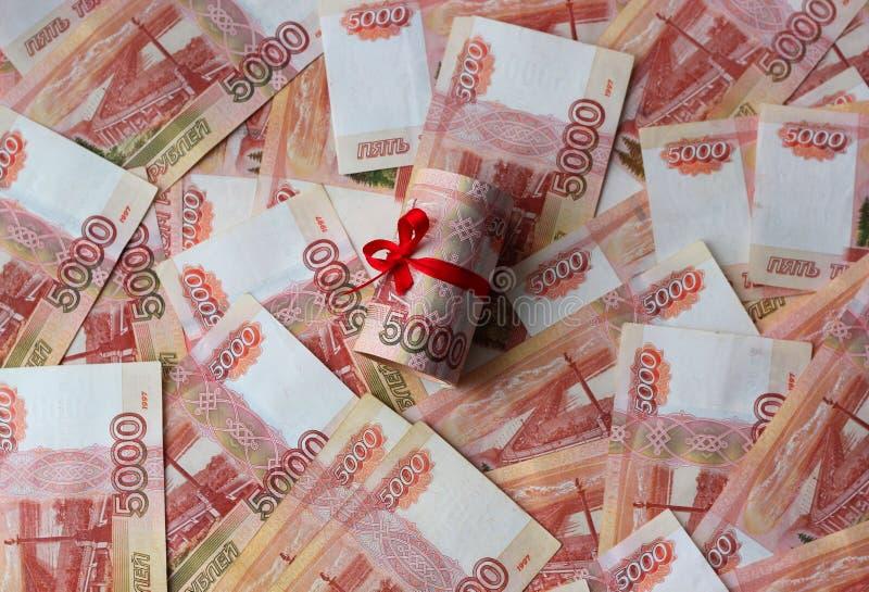 Ryska pengar 5000 rubel som vrids in i ett r?r och binds med ett band, p? en kul?r bakgrund royaltyfria foton