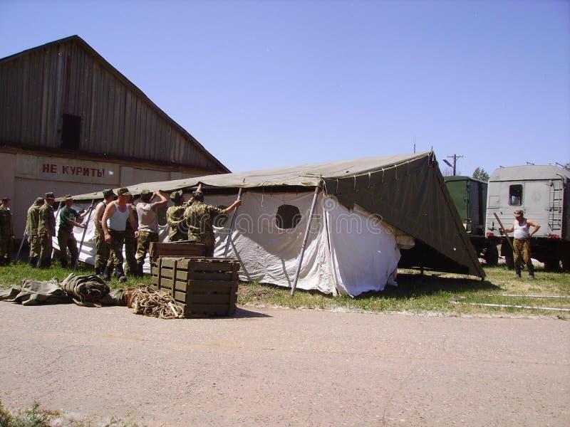Ryska soldater ställde in ett tält för militärövningar I bakgrunden är militär utrustning Ordna till för någon uppgift arkivfoton