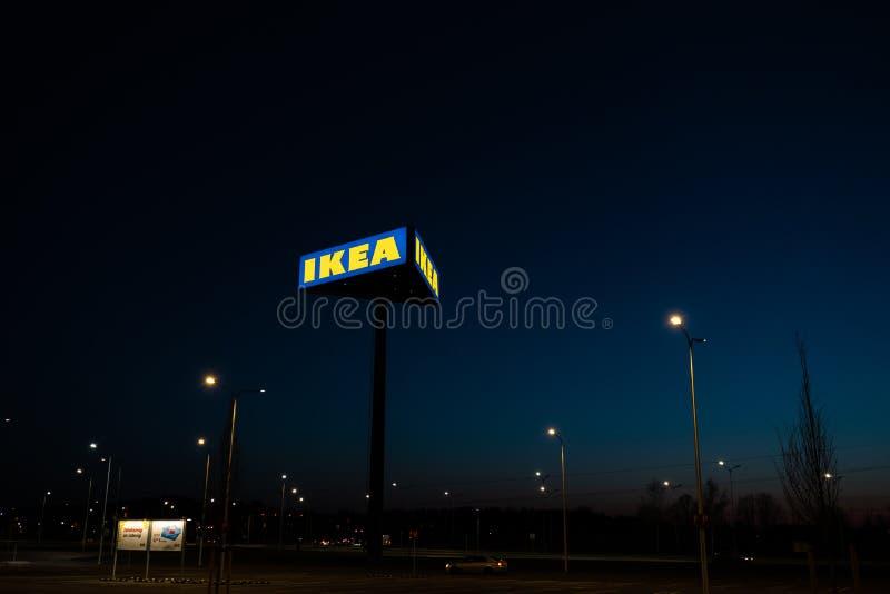 RYSKI, LATVIA, KWIECIE? - 3, 2019: IKEA oznakuje znaka podczas ciemnego wiecz?r i meandruje - niebieskie niebo w tle fotografia stock