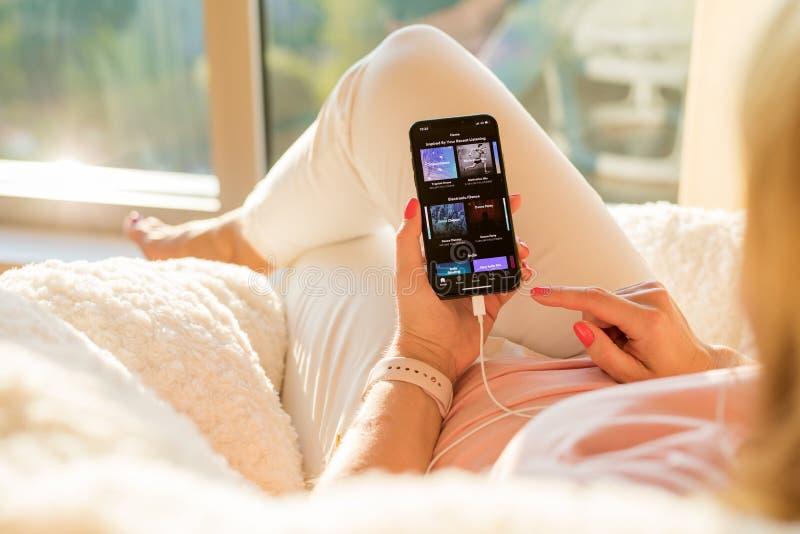 Ryski, Latvia, Lipiec - 21, 2018: Kobieta używa Spotify app na telefonie komórkowym obraz stock