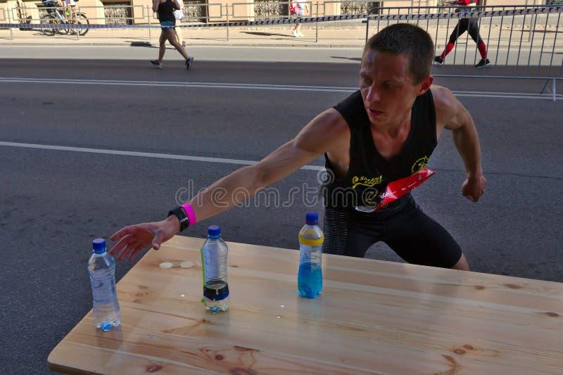 Ryski, Latvia, Maj - 19 2019: Kaukaski elity biegacza Tommy gmeranie dla sport?w pije fotografia royalty free