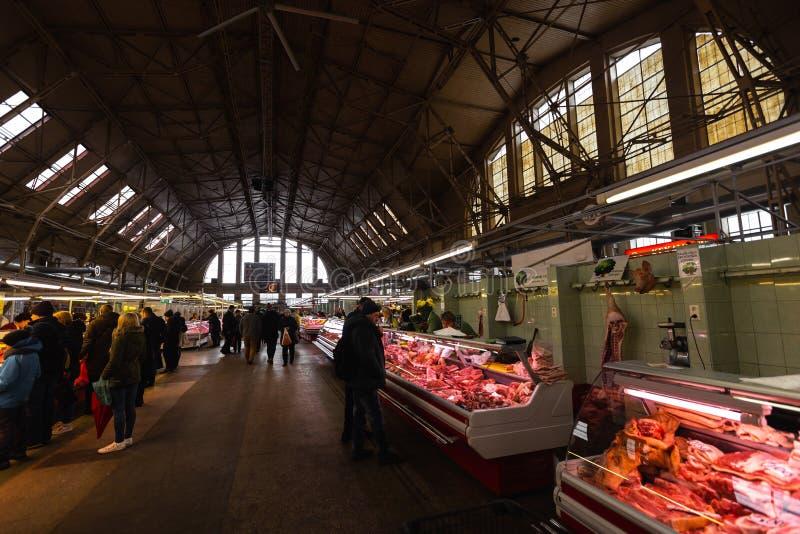 RYSKI, LATVIA, MARZEC - 16, 2019: Ryski Środkowego rynku mięsny pawilon, ludzie kupuje świeżą żywność - Poprzedni sterowów hangar obrazy royalty free