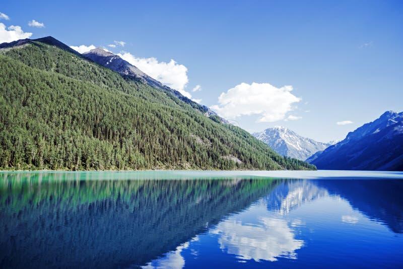 Ryssland Altai, bergen, sjön Kucherla reflexion av berg med snö-korkade maxima i kristallklart vatten royaltyfri foto