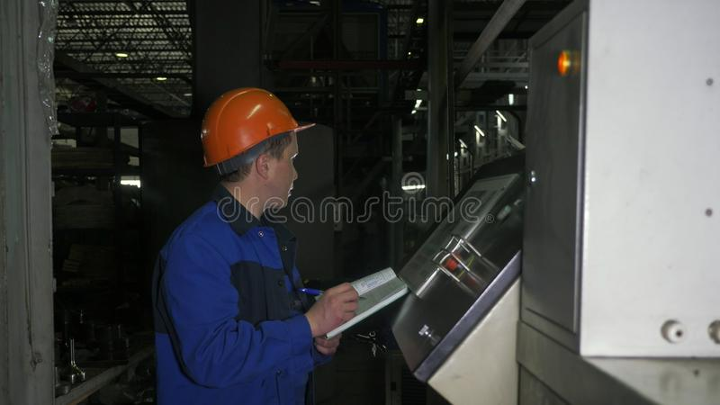 RYSSLAND ANGARSK - JUNI 8, 2018: Operatören övervakar kontrollbordet av produktionslinjen Tillverkning av plast- vattenrör arkivfoto