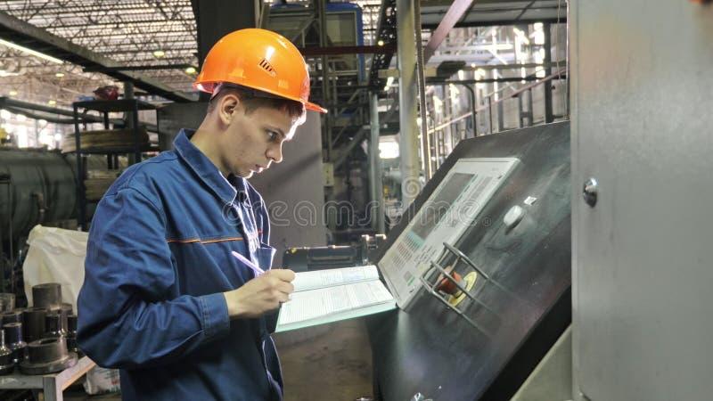 RYSSLAND ANGARSK - JUNI 8, 2018: Operatören övervakar kontrollbordet av produktionslinjen Tillverkning av plast- vattenrör royaltyfri fotografi