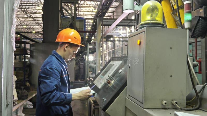 RYSSLAND ANGARSK - JUNI 8, 2018: Operatören övervakar kontrollbordet av produktionslinjen Tillverkning av plast- vattenrör fotografering för bildbyråer