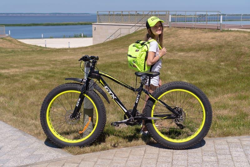 Ryssland Bolgar - Juni 09, 2019 Kol Gali Resort Spa: Barnflickan med en cykel GTX med en ryggsäck i hennes händer står på kusten arkivbilder