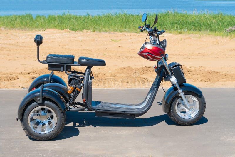 Ryssland Bolgar - Juni 08, 2019 Kol Gali Resort Spa: Tre-rullad elektrisk motorcykel på stranden Gå på en elektrisk sparkcykel in arkivfoto