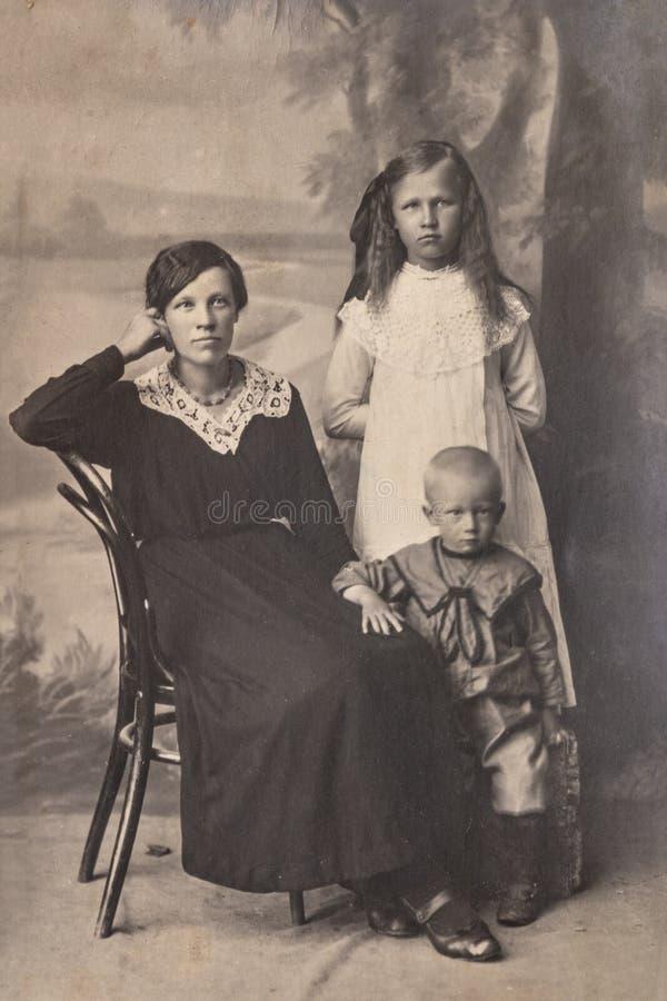 RYSSLAND - CIRCA 1905-1910: En stående av den unga kvinnan med barn i studion, Tappning Carte de Viste Edwardian erafoto royaltyfria foton
