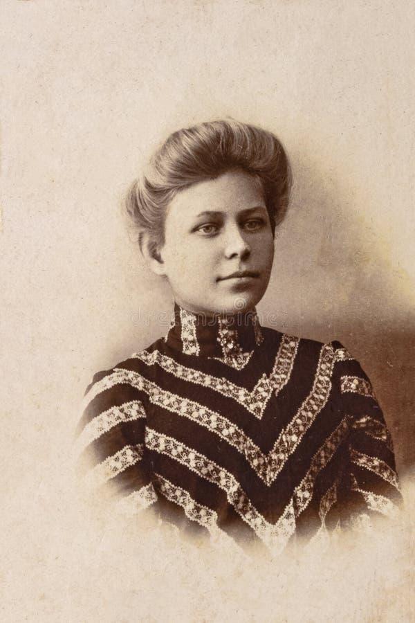 RYSSLAND - CIRCA 1905-1910: En stående av den unga kvinnan, Tappning Carte de Viste Edwardian erafoto arkivbilder