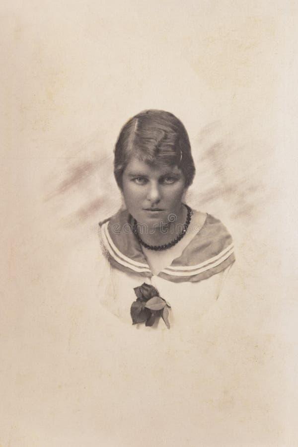 RYSSLAND - CIRCA 1916: En stående av den unga kvinnan, Tappning Carte de Viste Edwardian erafoto arkivfoton