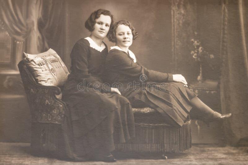 RYSSLAND - CIRCA 20-tal: Sköt av två unga kvinnor i studion, Tappning Carte de Viste Edwardian erafoto arkivfoto