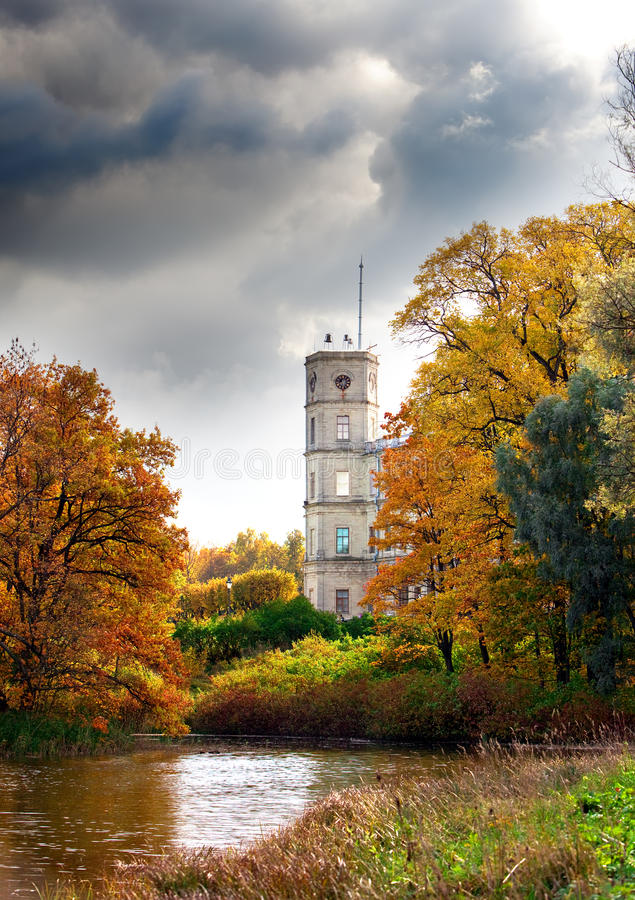 Ryssland Gatchina, det ljusa höstträdet parkerar in nära en slott. Cityscape royaltyfri fotografi