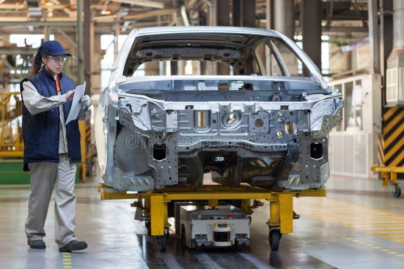Ryssland Izhevsk - December 15, 2018: LADA Automobile Plant Izhevsk Den kvinnliga arbetaren kontrollerar kroppen av en ny bil royaltyfri foto