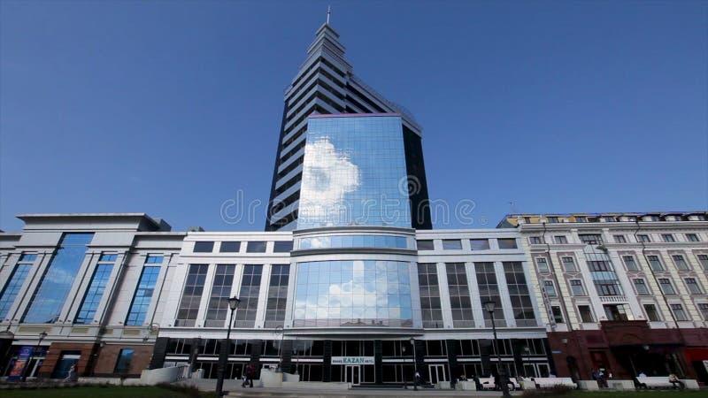Ryssland - Kazan, 1 Oktober 2018: Tid schackningsperiod av folk som framme går av modernt affärscentrum i Kazan, blå himmel arkivbild