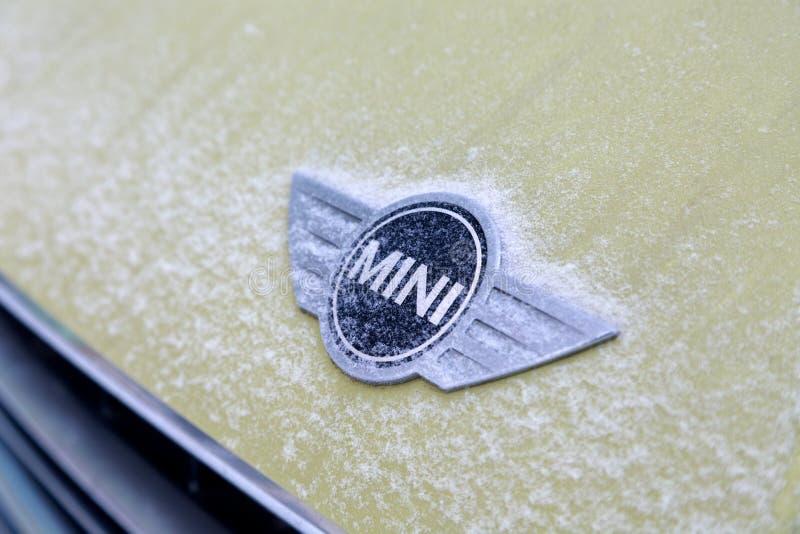 Ryssland Kemerovo 2019-01-07 täckte den nära sikten av emblemet för den Mini Cooper billogoen på den gula Mini Cooper bilen snö royaltyfri bild