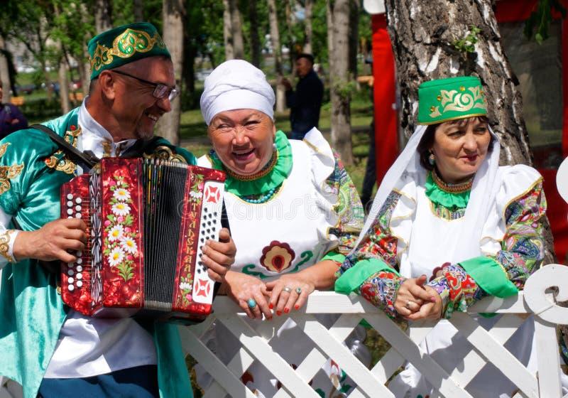 Ryssland Magnitogorsk, - Juni, 15, 2019 En man med ett dragspel och kvinnor i nationella dräkter av Bashkortostan och Tatarstan - royaltyfri fotografi