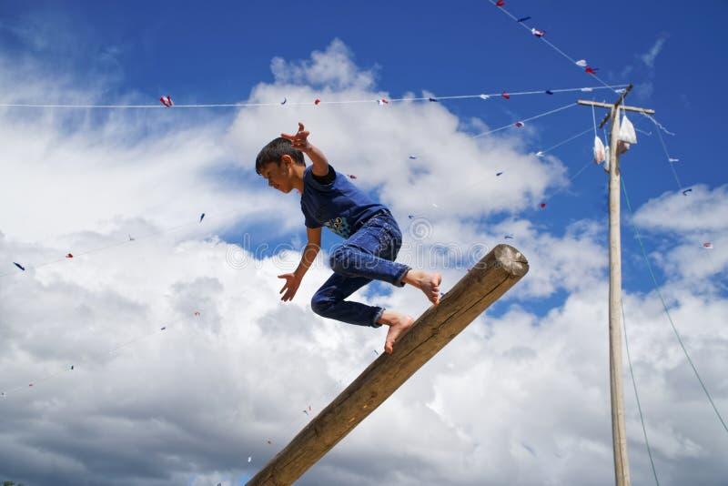 Ryssland Magnitogorsk, - Juni, 15, 2019 Pojken spelar nationella lekar, hopp från en journal, under Sabantuy - den nationella fer royaltyfria bilder