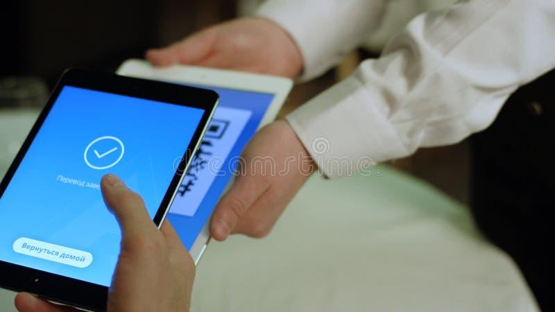 Ryssland Moskva - Maj 2018: Betala en restaurang med bitcoinpengar med en smartphoneapparat wirelessly materiel betalning royaltyfri fotografi