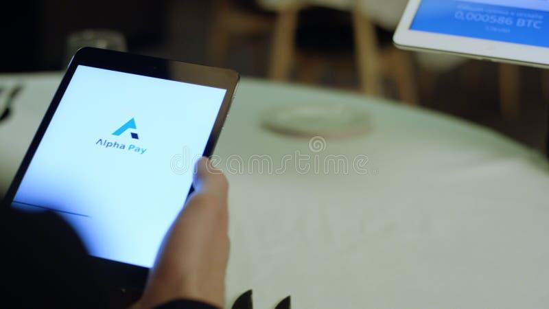 Ryssland Moskva - Maj 2018: Betala en restaurang med bitcoinpengar med en smartphoneapparat wirelessly materiel betalning arkivbild
