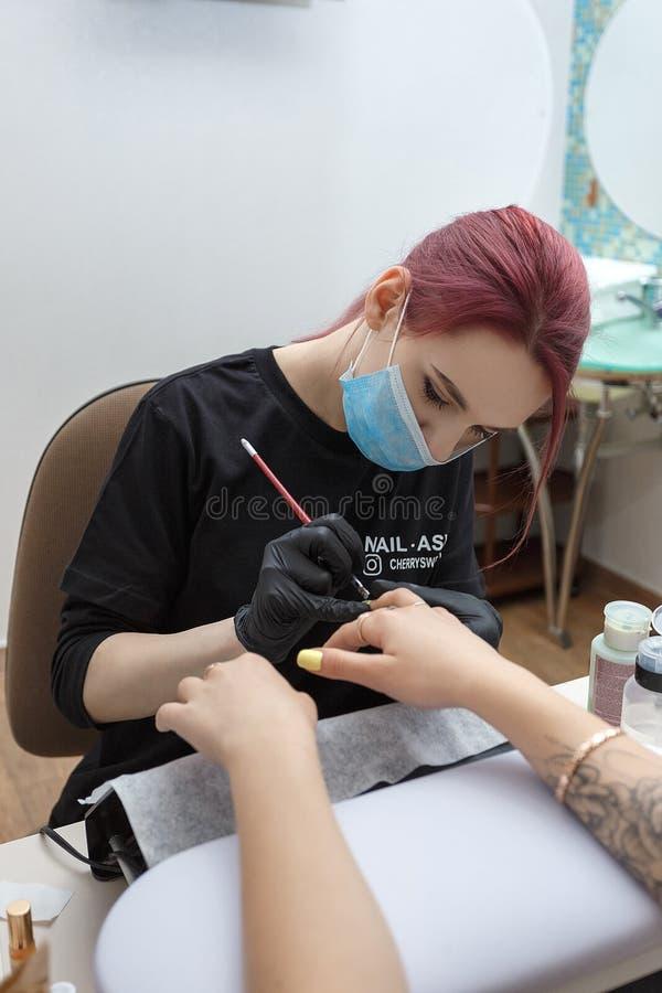 Ryssland Moskva, 18 Maj 2019 Spika den bärande maskeringen för förlagen, och svarta handskar som applicerar borsten på akryl, spi arkivbild