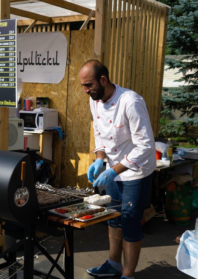 Ryssland Moskva, 26-28th Juli 2019, BBQ-festival i Moskva, Sokolniki parkerar Manlig kock i blåa handskar som lagar mat kött på s arkivfoto