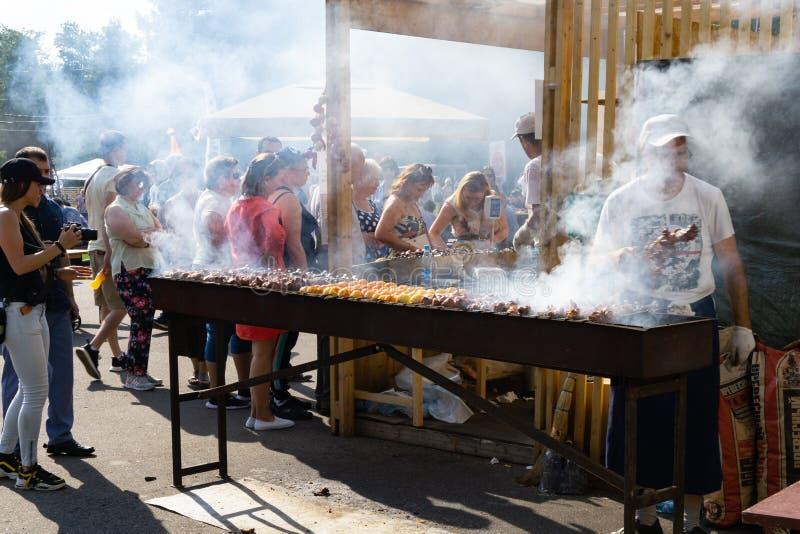 Ryssland Moskva, 26-28th Juli 2019, BBQ-festival i Moskva, Sokolniki parkerar Manlig kock som lagar mat kött- och potatisstundgru arkivfoto