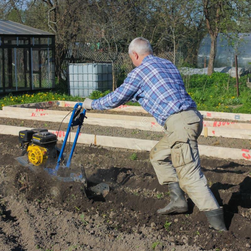 05/25/2012 Ryssland Nikolsky Bonden plogar jordningen med ettkvarter Ploga grouen royaltyfri foto