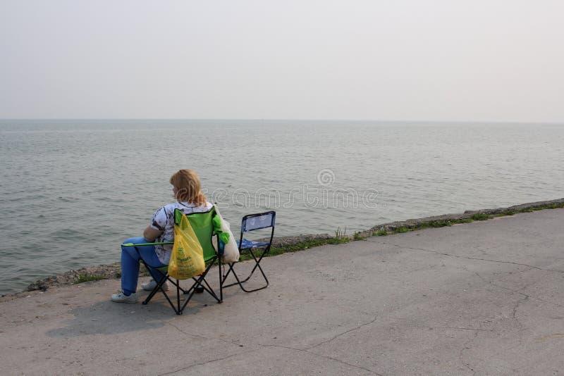 Ryssland Novosibirsk, Juli 21, 2019: en kvinna som sitter på sjösidan som vilar i morgonen på behållaren arkivfoto