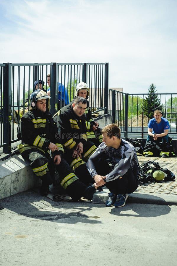 Ryssland Novosibirsk - 2 Juni, 2018: indikativ konkurrens av yrkesmässiga brandmän och räddare skyddande dräkt för brand royaltyfri bild