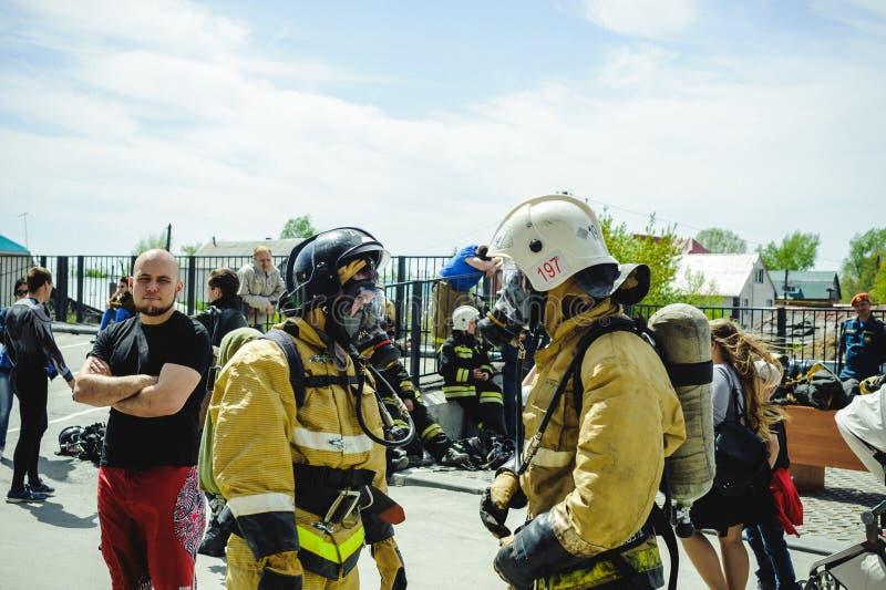 Ryssland Novosibirsk - 2 Juni, 2018: indikativ konkurrens av yrkesmässiga brandmän och räddare skyddande dräkt för brand royaltyfria bilder