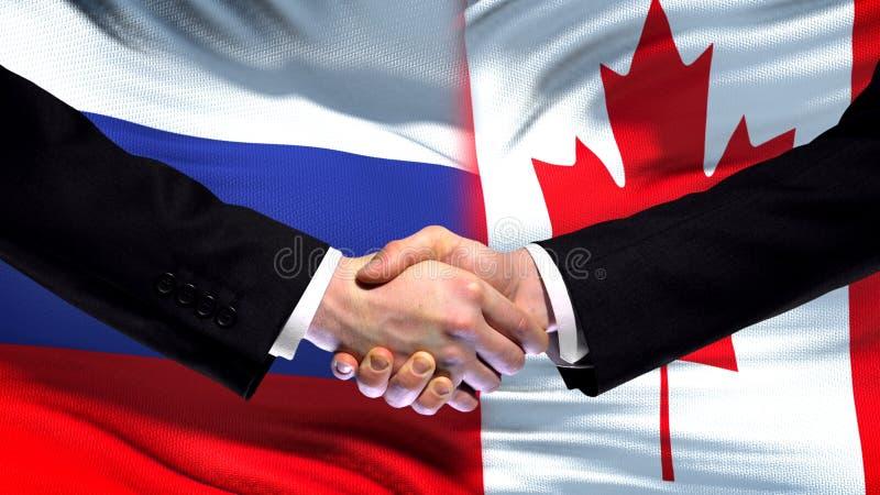 Ryssland och Kanada handskakning, internationell kamratskaptoppmöte, flaggabakgrund arkivfoto